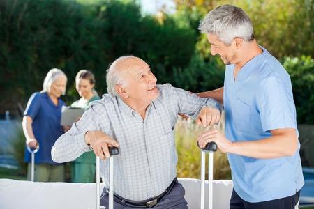 personas ayudando: Los cuidadores masculinos y femeninos Ayudando a las personas de edad avanzada