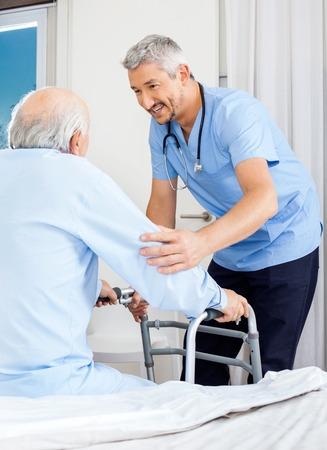 personas ayudando: Portero Ayudar al hombre mayor a utilizar Andador Foto de archivo