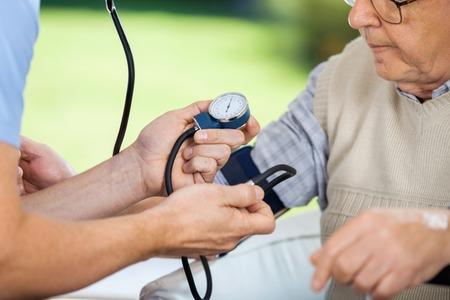 eldercare: Male Caretaker Measuring Blood Pressure Of Elderly Man Stock Photo