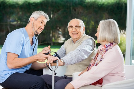 eldercare: Woman Looking At Male Doctor Measuring Blood Pressure Stock Photo