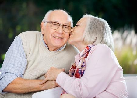 pareja besandose: Mujer mayor que se besan en la mejilla Mans Foto de archivo