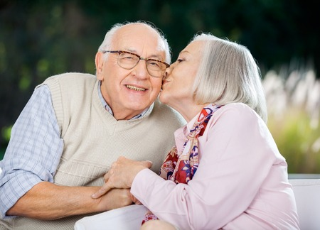elderly adults: Senior Woman Kissing On Mans Cheek