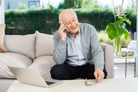 特別養護老人ホームのポーチで、スマート フォンに答えるシニア男性