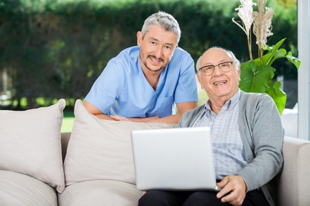 Happy Nurse And Senior Man With Laptop photo