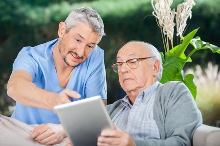 Infermiere che mostra qualcosa al Uomo maggiore sulla Digital Tablet Archivio Fotografico