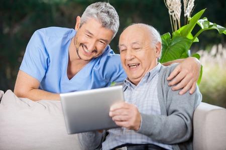 Infermiere E anziano uomo ridere guardando PC Digital Archivio Fotografico
