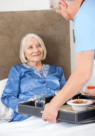 Caretaker Serving Breakfast To Happy Senior Woman photo