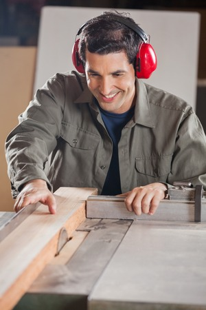 woodworker: Happy Carpenter Cutting Wooden Plank With Tablesaw Stock Photo