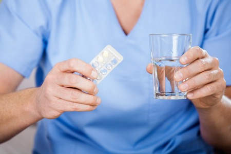Male Caretaker Holding Blister Pack And Glass Of Water photo