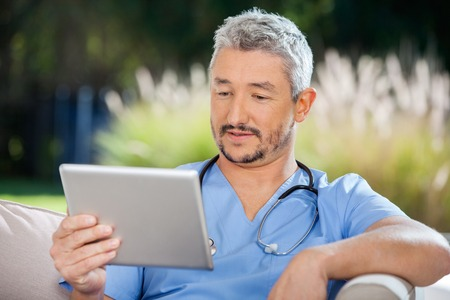 Male Doctor Looking At Tablet PC photo