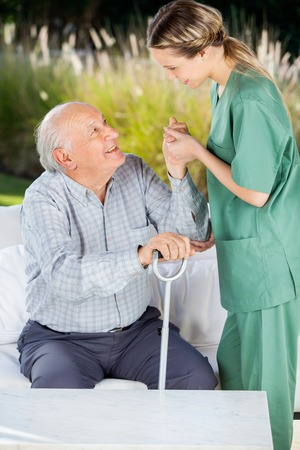 Female Caretaker Helping Elderly Man To Get Up From Couch