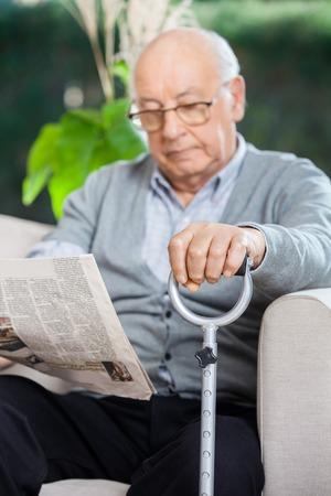 cane sofa: Elderly Man Reading Newspaper At Nursing Home Porch