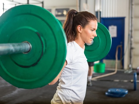 weightlifting equipment: Fit Woman Lifting Barbell in Gym Stock Photo