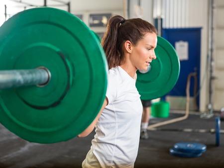 deportistas: Mujer apta de elevaci�n pesas en el gimnasio