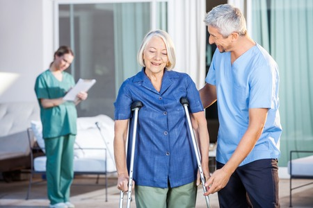 mobility nursing: Male Nurse Helping Senior Woman To Use Crutches