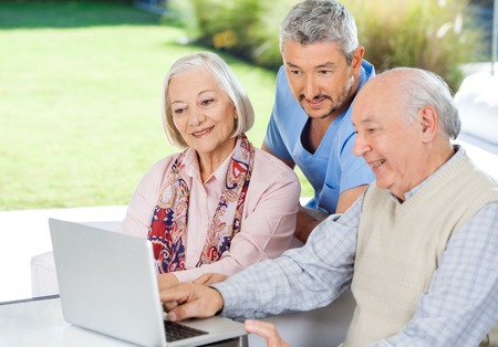 Caretaker Watching Senior Couple Using Laptop
