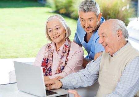 Hausmeister beobachten ältere Paare unter Verwendung des Laptops