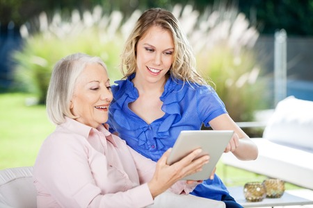 Happy Grandmother And Granddaughter Using Digital Tablet Stock Photo