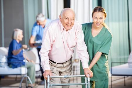 Vrouwelijke Caretaker Helping Senior Man In Het gebruik van Zimmer Frame Stockfoto