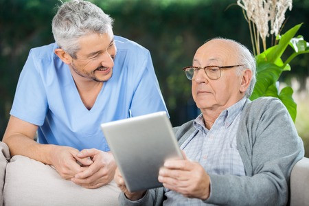 Maschio Custode Rivolto verso l'anziano uomo utilizzando tablet computer Archivio Fotografico