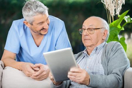 chăm sóc sức khỏe: Nam Caretaker Nhìn Tại Senior Man Sử dụng Tablet Computer