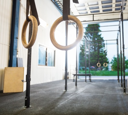 strong chin: Gymnastic Rings Hanging in Cross Fitness Gym Stock Photo