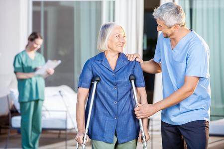 Glücklich Männlich Hausmeister älterer Frau hilft beim Gehen