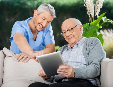 an elderly person: Enfermera feliz Ayudar Hombre Mayor En Uso de Tablet Computer Foto de archivo