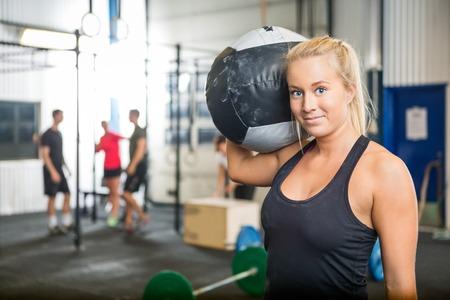 Frauen-tragende Medizinball Am Crossfit Turnhalle