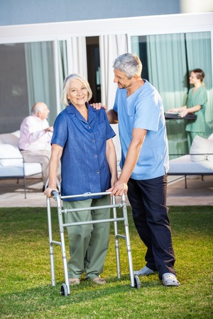 assisted: Senior Woman Being Assisted By Male Caretaker