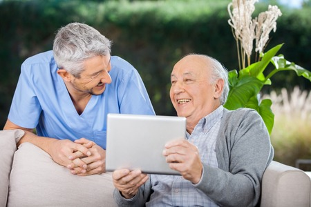 residents: Male Caretaker And Senior Man Laughing While Using Tablet Comput