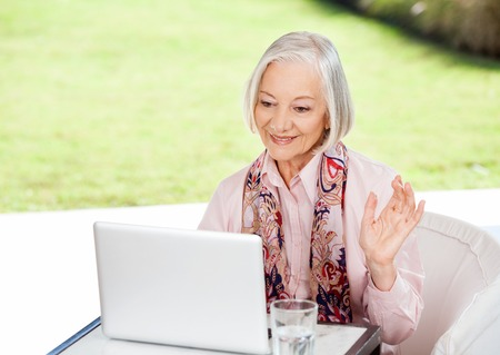 conferencing: Senior Woman Waving While Video Conferencing On Laptop Stock Photo