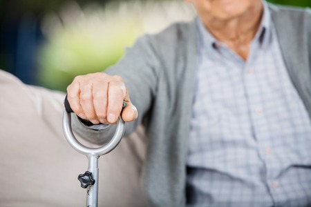 guy with walking stick: Midsection Of Senior Man Holding Metal Walking Stick Stock Photo
