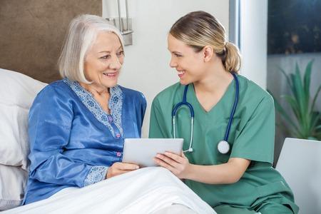 haushaltshilfe: Gl�ckliche Krankenschwester und �ltere Frau, die Tablette-PC Lizenzfreie Bilder