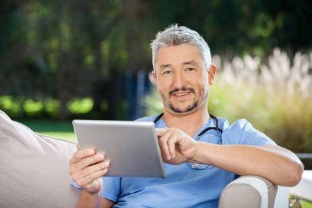 Male Caretaker Using Tablet Computer photo