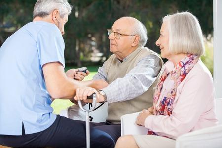 eldercare: Male Doctor Measuring Blood Pressure Of Senior Man
