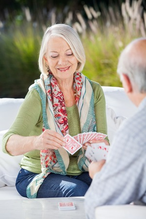playing card: Happy Senior Woman Playing Cards With Man
