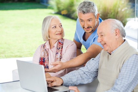 eldercare: Male Caretaker Showing Something To Senior Couple On Laptop