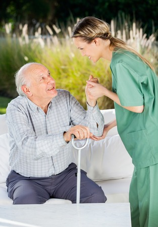 Female Nurse Helping Senior Man To Get Up From Couch photo