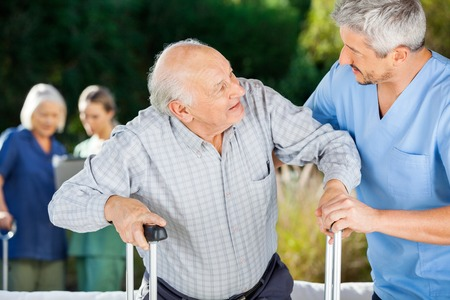 Male And Female Nurses Helping Senior People Stock Photo