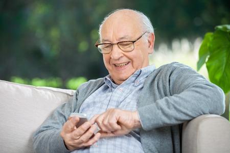 笑みを浮かべて年配の男性テキスト メッセージ携帯電話を通じて