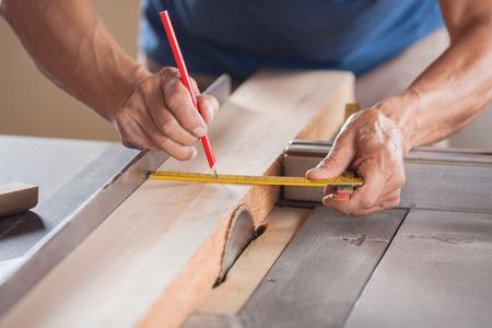 herramientas de carpinteria: Imagen recortada de carpintero Medici�n Madera En tablesaw Foto de archivo
