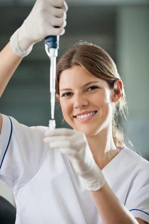 research facilities: Female Scientist Filling Liquid Into Test Tube Stock Photo