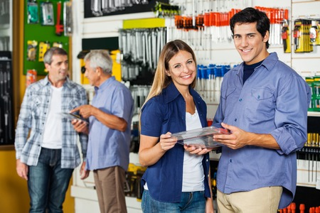 Happy Couple Holding Tool Set In Hardware Store photo