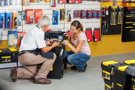 couching: Salesman Showing Tools To Customer In Shop Stock Photo