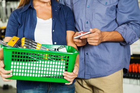 Couple Carrying Basket Full Of Tools In Store photo