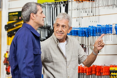 Customer Pointing While Looking At Hardware Shop Vendor