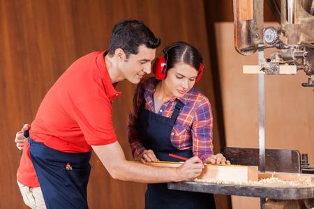 Carpenters Measuring Wood In Workshop photo
