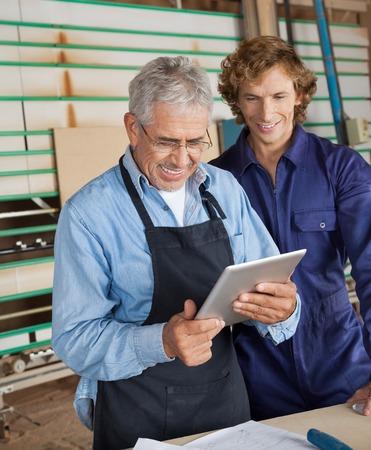 coworker: Carpenter Using Digital Tablet With Coworker