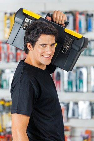 shoulder carrying: Confident Man Carrying Toolbox On Shoulder In Store